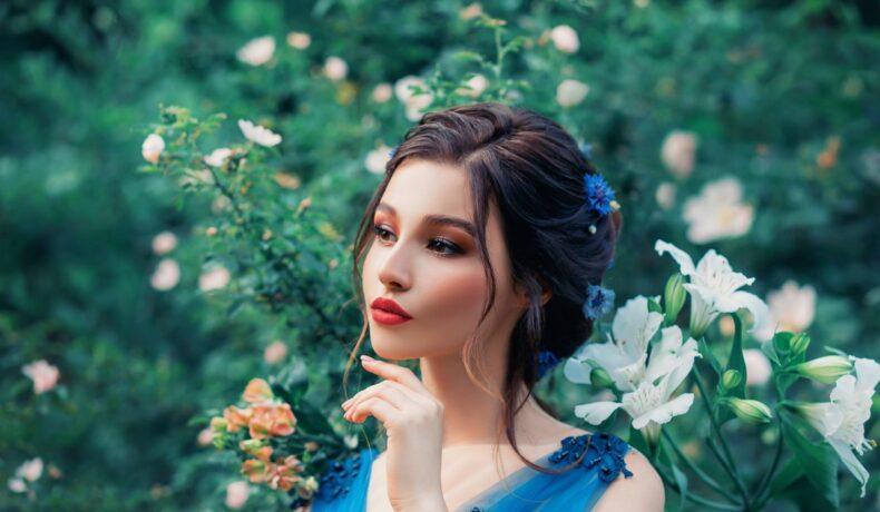 o femeie frumoasă cu părul prins care stă printre iarbă și flori albe, în timp ce ține o mână sub bărbie și se gândește la acele zodii vulnerabile