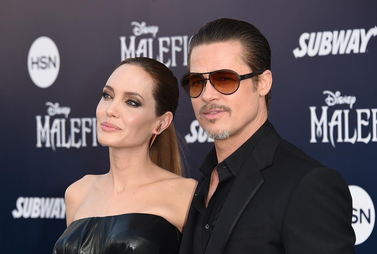 Angelina Jolie și Brad Pitt la premiera Maleficent. Amândoi poartă negru. Brad Pitt e îmbrăcat într-un costum, Angelina într-o rochie neagră fără bretele