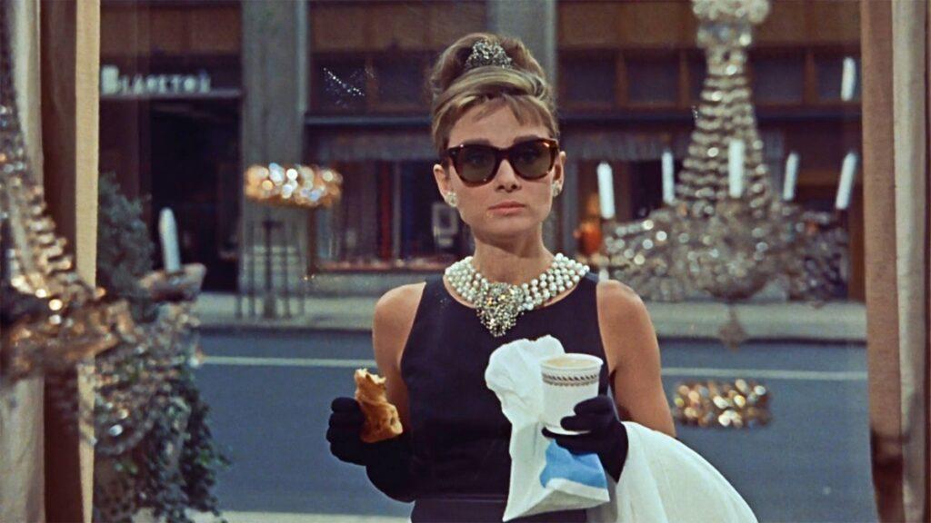 Audrey Hepburn în filmul Breakfast at Tifannys. Poartă celebra rochie neagră, cu perle și ochelari de soare. Stă în fața vitrinei magazinului și mănâncă