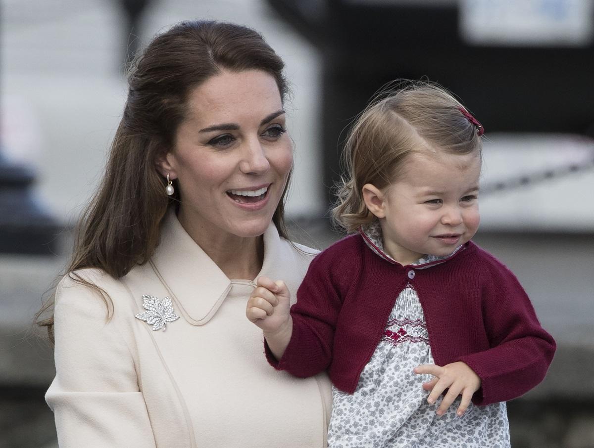 Kate Middleton și Prințesa Charlotte, Canada, 2016. Kate poartă o haină bej, Charlotte poartă o rochie albă și o bluză vișinie