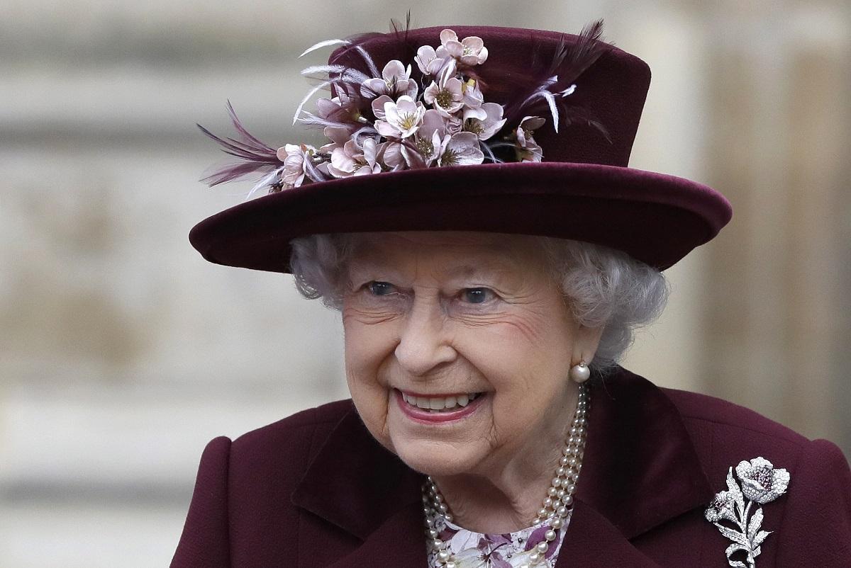 Regina Elisabeta la un eveniment din cadrul Westminster Abbey, 2018. Poartă un costum grena, accesorizat cu o pălărie grena, cu flori roz, fundal bej