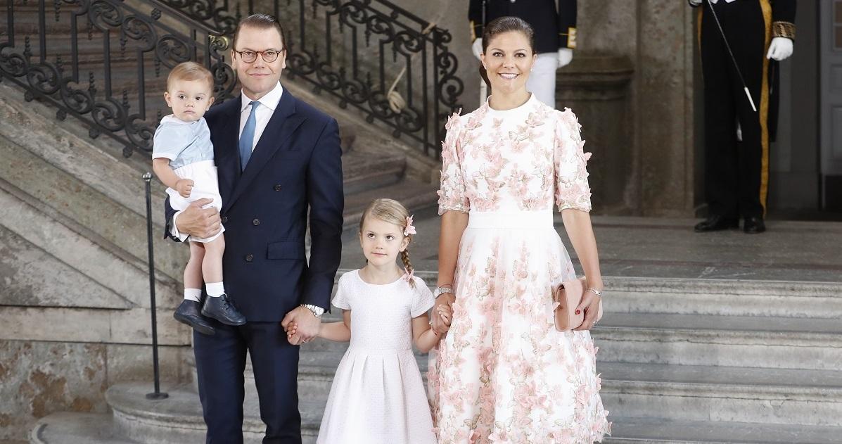 Prințesa Victoria, prințul Daniel, Prințesa Estelle și Prințul Oscar ai Suediei în 2017, când Victoria a ămolinit 40 de ani. Fetele poartă roz, Daniel poartă un costum închis la culoare, fundal cu scari
