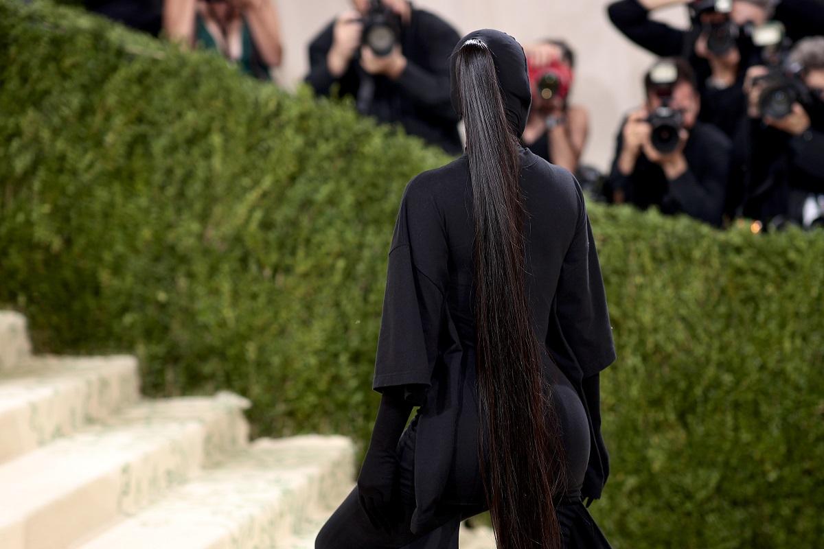 Părul lui Kim Kardashian la Met Gala 2021 în timp ce urcă pe scări și poartă o ținută neagră