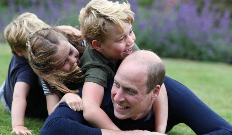 Prințul William se joacă alături de Prințul George, Prințesa Charlotte și prințul Louis. Toți trei sunt îmbrăcați în albastru închis și se joacă pe iarbă