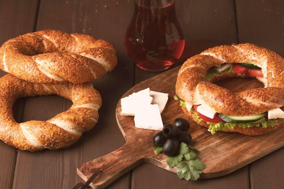 Trei covrigi turcești Simit, unul făcut sandviș, pe un suport de lemn, alătur de un pahar cu ceaii