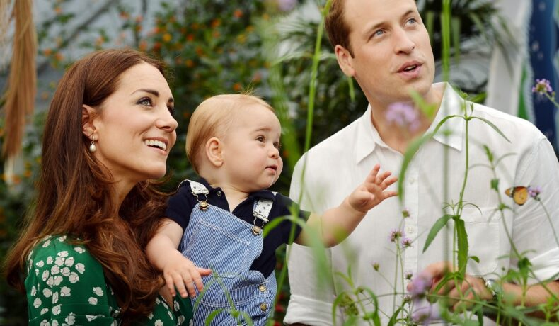 Prințul William, Kate Middleton și Prințul George. Ea poartă o rochie verde, el poartă bej, George poartă o salopetă albastră