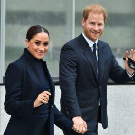 Meghan Markle și Prințul Harry în New York, pe stradă. Amândoi sunt îmbrăcați în negru și fac cu mâna la camere