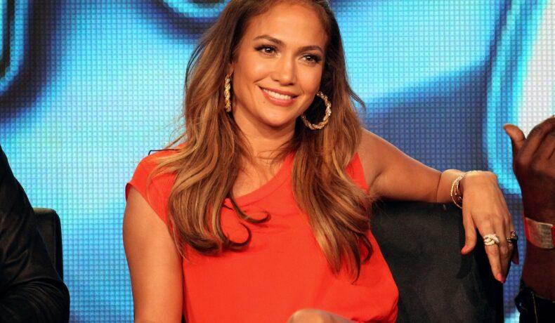 Jennifer Lopez în juriul American Idol, 2012. E îmbrăcată într-o rochie lejeră portocali. Are părul desfăcut, cu cercei mari