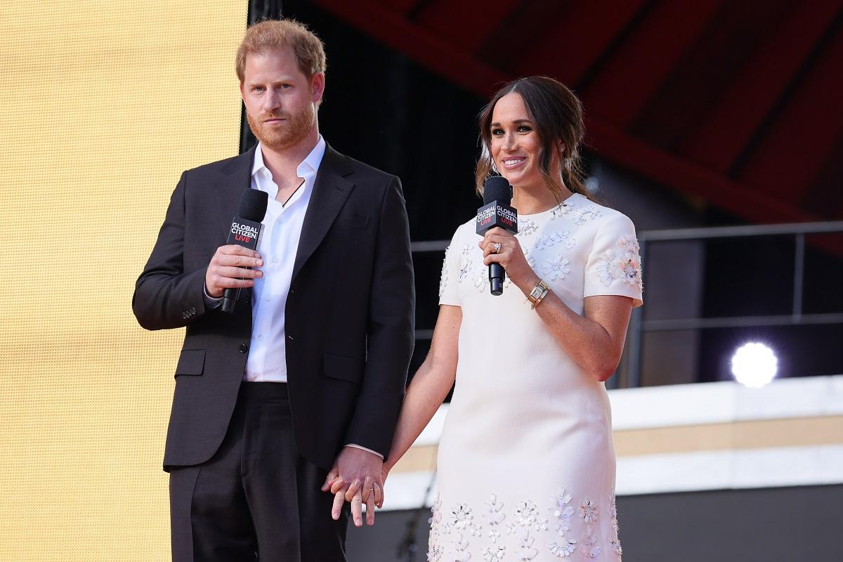 Prințul Harry și Meghan Markle la Global Citizen Live, 2021. Pe scenă, el a purtat un costum negru și o cămașă albastră. Ea a purtat o rochie albă, cu mânecă scurtă
