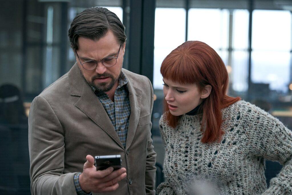 Leonardo DiCaprio și Jennifer Lawrence în filmul on't Look Up. Se uită amândoi la un telefon Ea e roșcată și îmbrăcată în gri, el e într-un costum gri