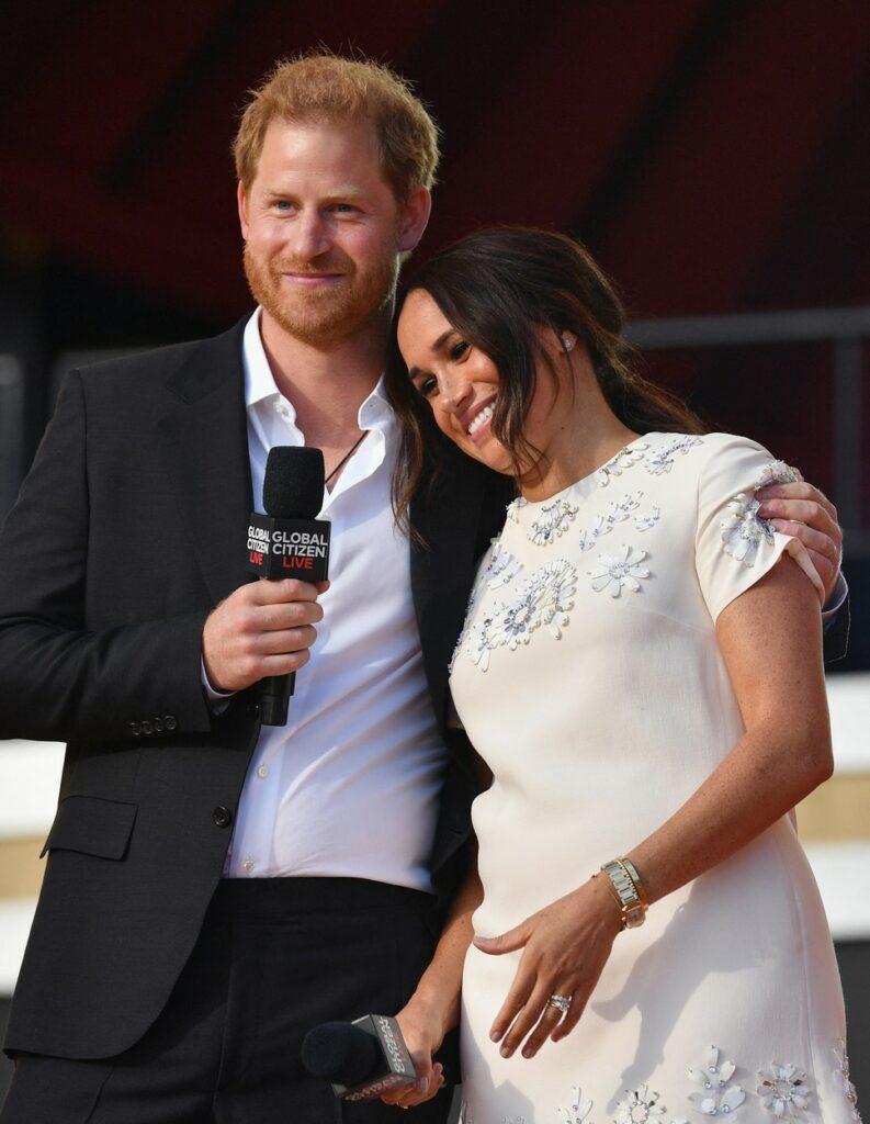 Ducii de Sussex, îmbrăcați elegant, în haine deschide la culoare, pe scena Global Citizen Live