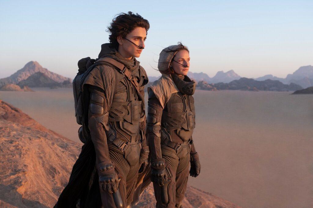 Film still cu Timothee Chalamet și Rebecca Ferguson, din filmul Dune, 2021. Ei sunt îmbrăcați în armuri negre, cu un fundal cu deșert