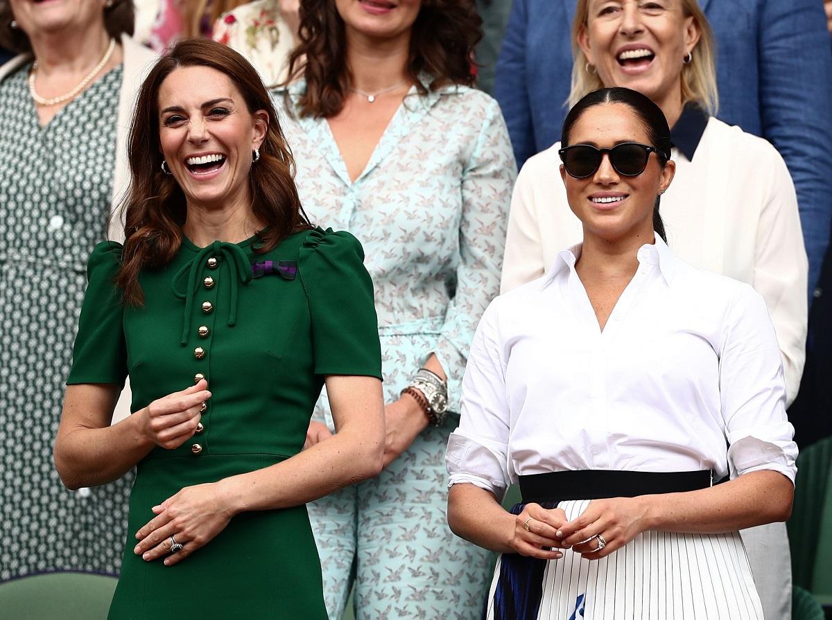 Kate Middleton și Meghan Markle, tribuna regală la Turneul de la Wimbledon, 2019. Kate poartă o rochie verde, Meghan Poartă o cămașă albă și o fustă cu o fundă neagră în talie, plus ochelari de soare
