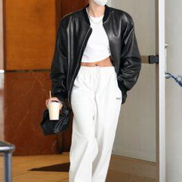 Hailey Bieber, îmbrăcată în haine sport, cu geacă din piele, pe stradă