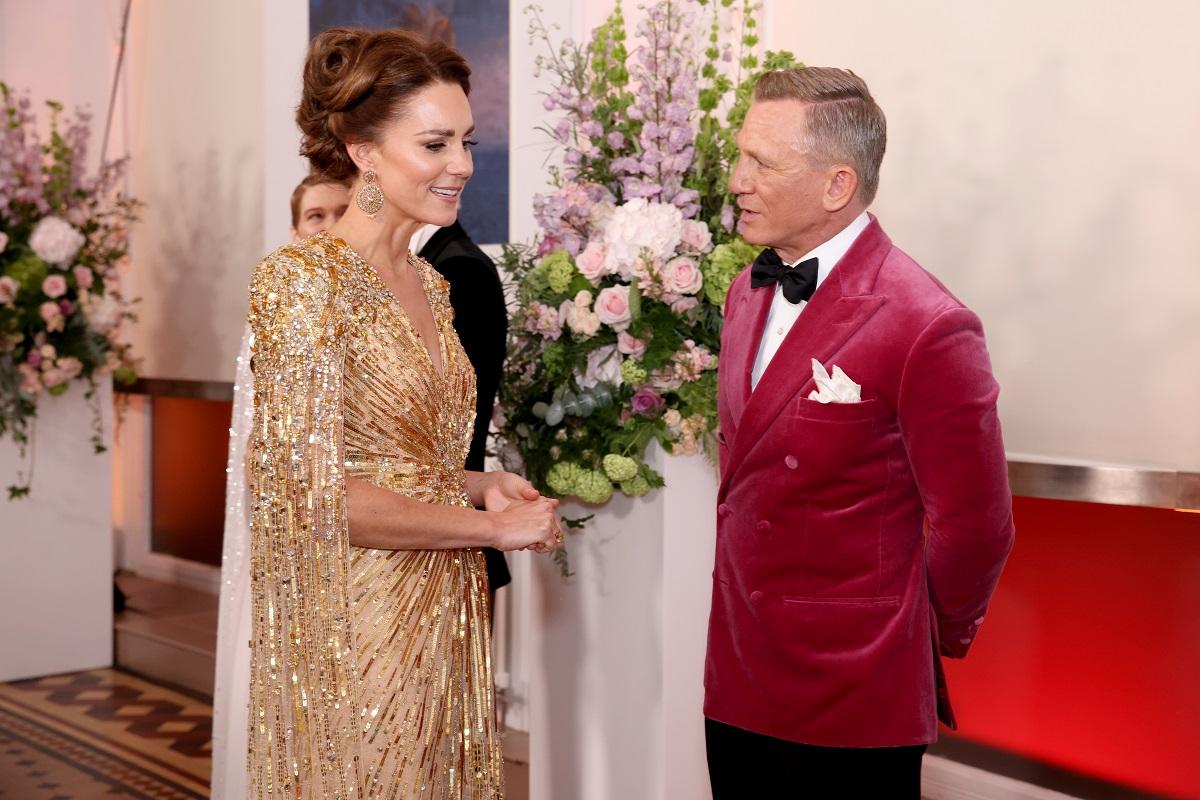 Kate Middleton și Daniel Craig, la premiera filmului No Time To Die, din 2021. Ea poartă o rochie aurie, cu mâneci până la pământ. Craig poartă o jachetă din catifea roz și pantaloni negri. Kate s-a numărat printre membrii Familiei Regale la premierele Bond de-a lungul anilor