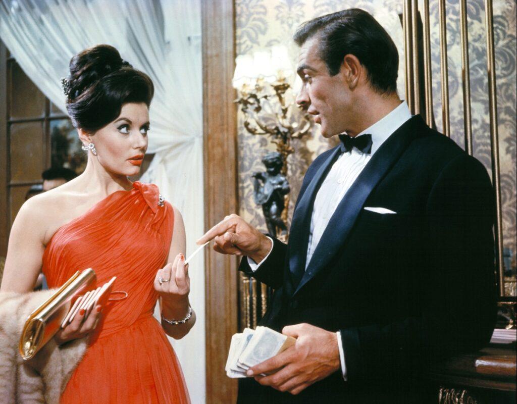 Sean Connery într-o imagine din Dr. No, primul film James Bond. Poartă un costum negru, bluză albă, și o femeie poartă o rochie roșie