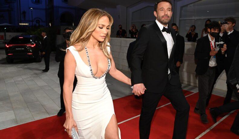 Jennifer Lopez și Ben Affleck la Festivalul de Film de la Veneția 2021. Ea poartă o rochie albă cu decolteu adânc și detaliu argintiu în zona pieptului, el poartă un costum negru