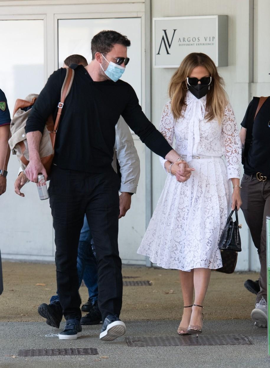 Jennifer Lopez și Ben Affleck, fotografiați în timp ce se țin de mână. Sunt îmbrăcați în haine elegante, demne de un eveniment luxos