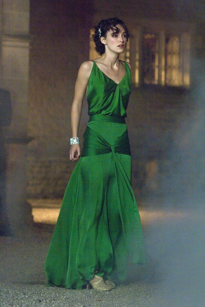 Keira Knightley în filmul Atonement, în celebra rochie verde. Are părul prins, poartă bijuterii și are o clădire în spate