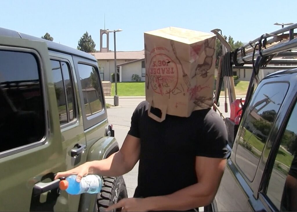 Logodnicul lui Britney Spears, Sam Asghari în timp ce deschide portiera la mașină și poartă pe cap o pungă de carton de cumpărături
