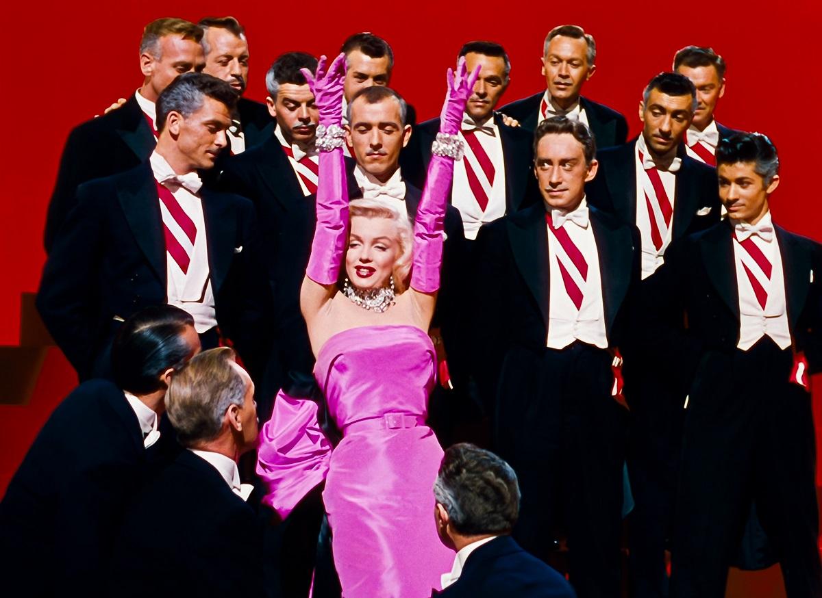 Marilyn Monroe în filmul Gentlemen Prefer Blondes. Poartă faimoasa rochie roz, înconjurată de bărbați în costume negre, cu cămpși albe, fundal roșu