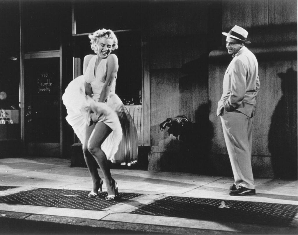 Marilyn Monroe în filmul The Seven Year Itch. Fotografie alb-negru. Poartă celebra rochie albă care se ridică