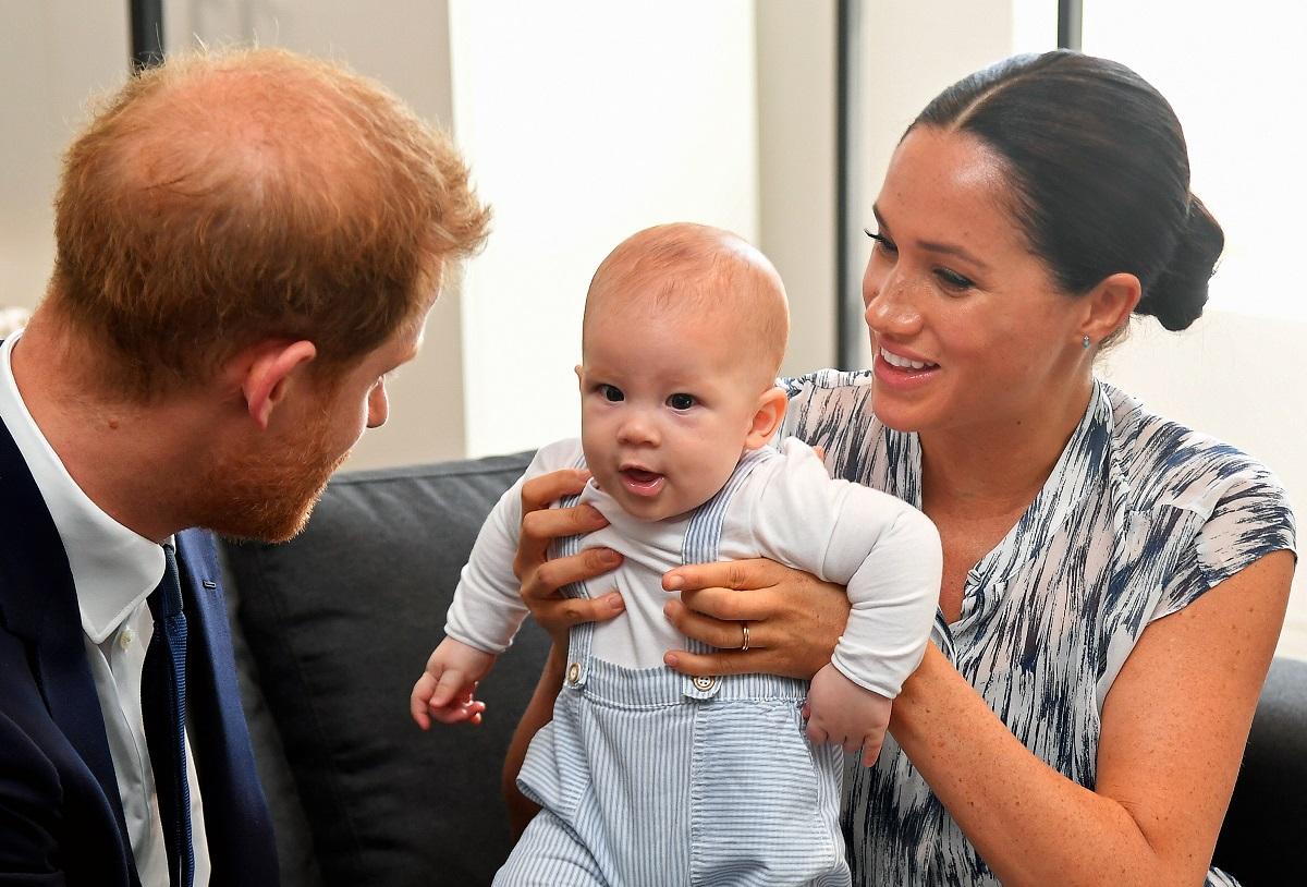 Prințțul Harry, Meghan Markle, Archie, în timpul unei vizite în CapeTown, Africa, 2019. Archie e îmbrăcat în alb, Harry în costum, Meghan într-o rochie cu gri
