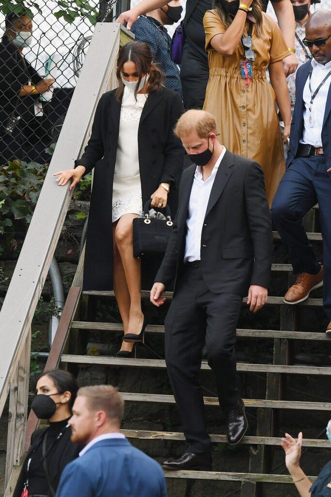 Prințul Harry și Meghan Markle coboară scările după Global Citizen Live. El poartă un costum negru, ea poartă o rochie albă, o haină neagră și geanta Lady Dior