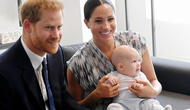Prințul Harry, Meghan Markle, Archie, în Africa de Sud, 2019. Archie e îmbrăcat în alb, Harry în costum negru, Meghan într-o rochie alb cu negru. Toți 3 stau pe canapea