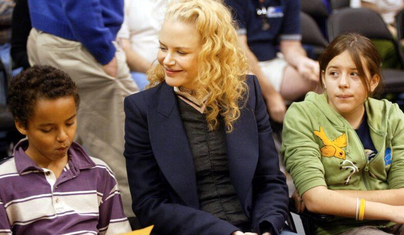 Nicole Kidman, Isabella Cruise și Connor Cruise, la un meci de baschet lakers, din anul 2004. Nicole poartă o jachetă albastru închis, Isabella are un hanorac cu guglă verde și Connor are o bluză în dungi albe și mov
