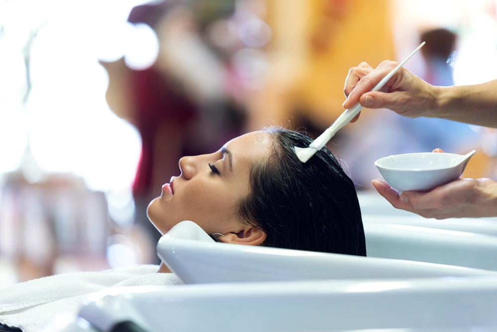 O femeie la un salon de înfrumusețare, care își face un tratament pentru păr