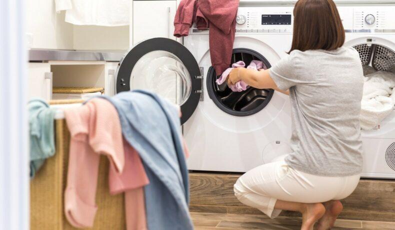 O femeie care pune haine în uscătorul de rufe