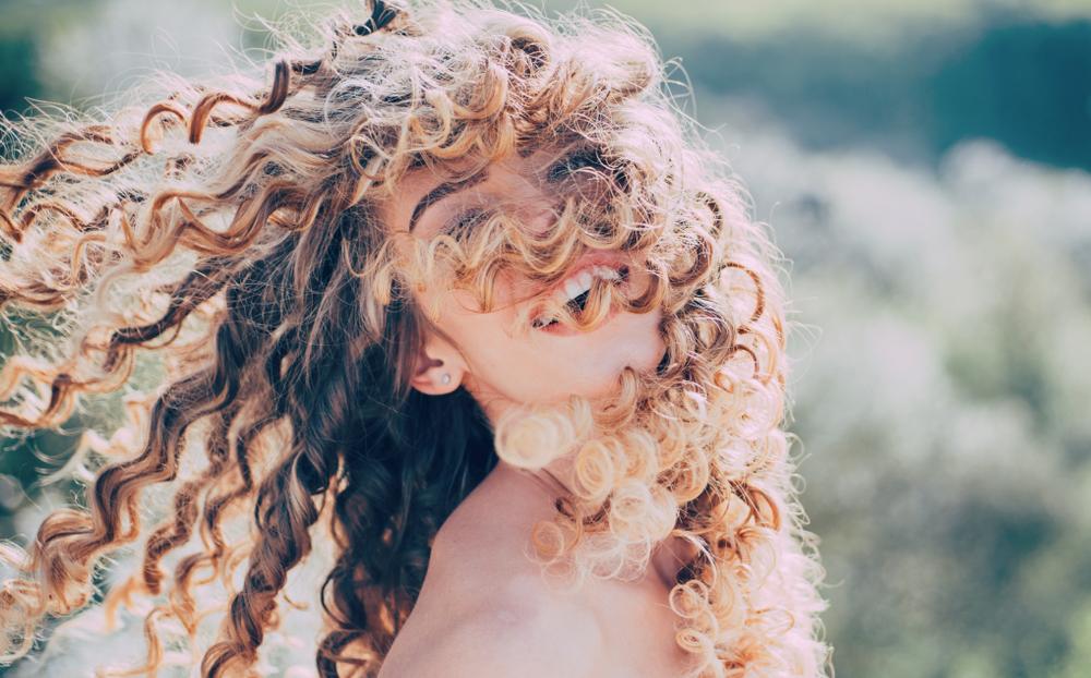 O femeie cu părul creț, cu buclele pe față, în natură