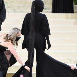 Kim Kardashian în timp ce stă cu spatele pe scările de la Met Gala 2021 și pozează