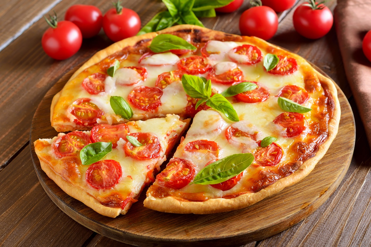 Pizza Margherita secționată pe un tocător de lemn, alături de roșii cherry și frunze de busuioc