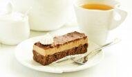 Porție de prăjitură cu nucă și cremă de ness pe o farfurie albă, decorată cu o bezea