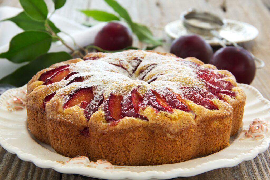 Prăjitura pufoasă cu prune, decorată cu zahăr pe un platou de servire