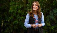 Kate Middleton în anul 2020, în timpul unui eveniment oficial din Londra. În natură, cu verdeață pe fundal, e îmbrăcată în uniformă de cercetaș, cu o cămașă albastră, vestă neagră și eșarfă la gât cu roșu