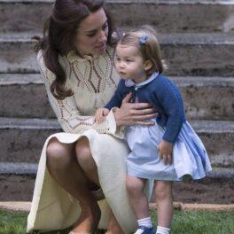 Kate Middleton și Prințesa Charlotte, împreună în Victoria, Canada, în anul 2016. Charlotte poartă o rochie albastră, Kate Middleton e îmbrăcată în bej. Ambele stau pe iarbă