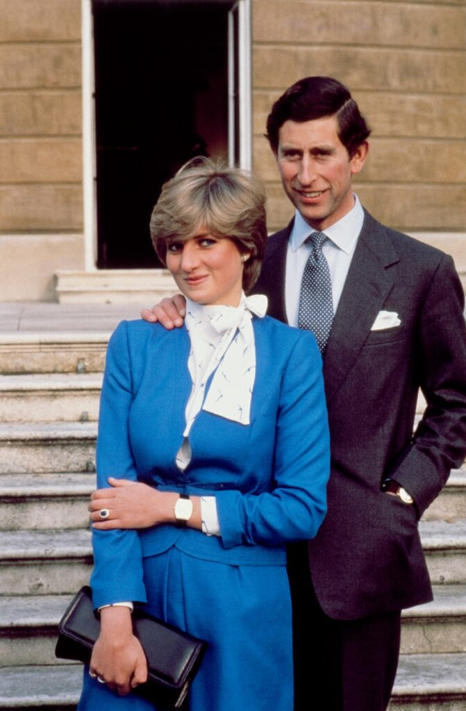 Prințul Charles și Prințesa Diana în ziua anunțului logodnei lor. Diana a purtat o rochie albastră cu accente albe și o geantă neagră. Charles a purtat un costum închis la culoare, bluză deschisă și o cravată albastră