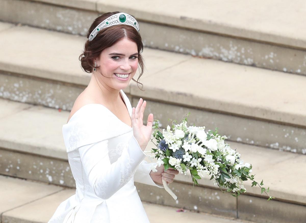 Prințesa Eugenie la nunta ei din 2018. E îmbrăcată în alb și poartă un buchet de flori albe în mână. Pe fundal scări