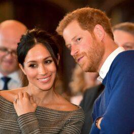 Prințul Harry și Meghan Markle la un eveniment din Cardiff, în anul 2018. El poartă un costum albastru, ea poartă o rochie bej, fără umeri