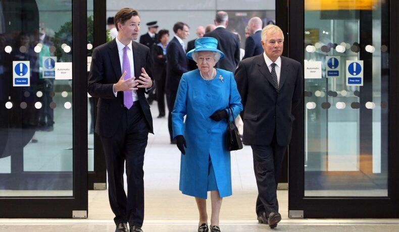 Regina Elisabeta revine în Marea Britanie în anul2 014, în aeroportul Heathrow, Londra. E îmbrăcată într-un costum albastru