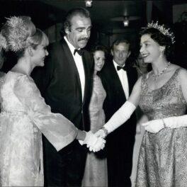 Regina Elisabeta, Sean Cpnnery și soția lui, în 1967, la premiera You Only Live Twice. Elisabeta poartă o rochie lungă și o coroană, Sean poartă un costum