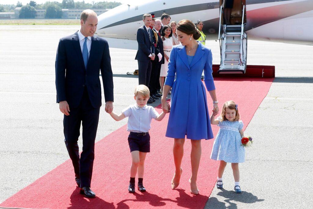 Kate Middleton și Prințul William, Prințul George, Prințesa Charlotte, covor roșu pe aeroport. Avion în spate, Kate poartă o rochie albastră