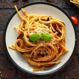 Spaghetti alla Norma pe o masă de lemn decorate cu frunze de busuioc