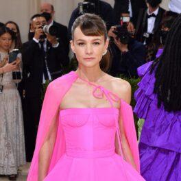 Carey Mulligan într-o rochie roz cu o pelerină pe covorul roșu la Met Gala 2021