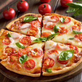 Pizza Margherita porționată în șase pe un platou de lemn