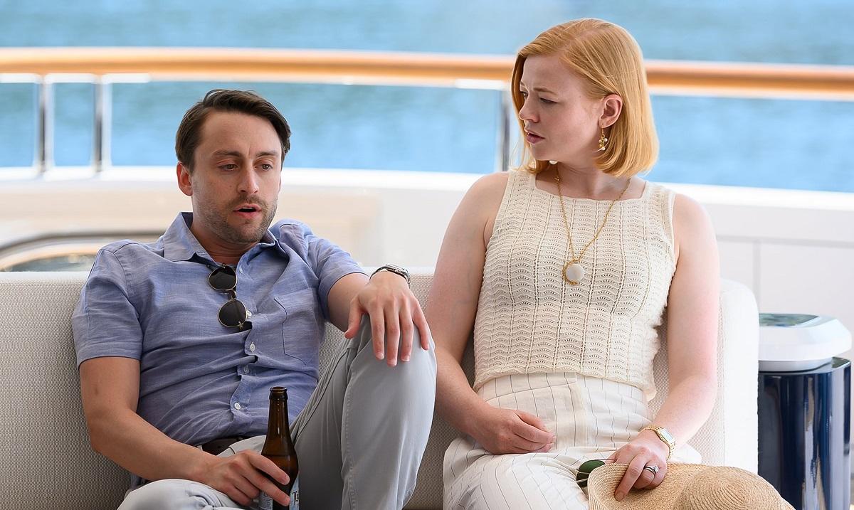 Imagine din sezonul 2 al serialului Succesiunea, cu Culkin și Snook. Stau pe un iaht, mare în spare, fundal alb. E poartă o cămașă albastră, ea poartă o bluză albă. Succesiunea e unul dintre cele mai așteptate seriale care apar în octombrie 2021