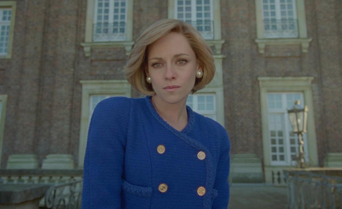 Imagine din filmul Spencer, 2021, cu kristen Stewart în rol principal. Prințesa Diana, costum albastru, nasturi aurii, fundal cu o clădire